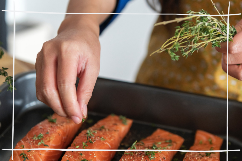 hand sprinkling herbs on fish fillets